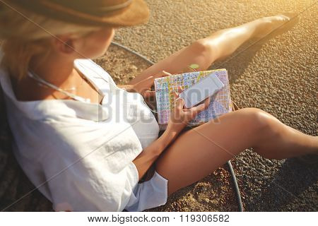 Female tourist chatting on cell telephone while sitting on the ground