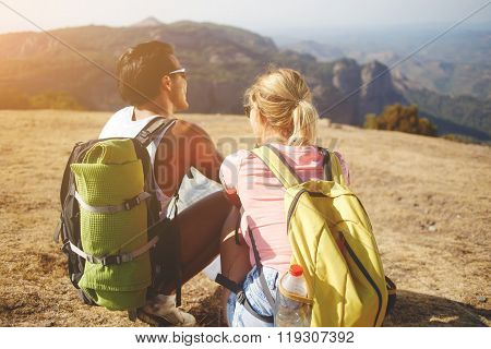 Back view of a young man and woman enjoying amazing nature landscape during their summer trip