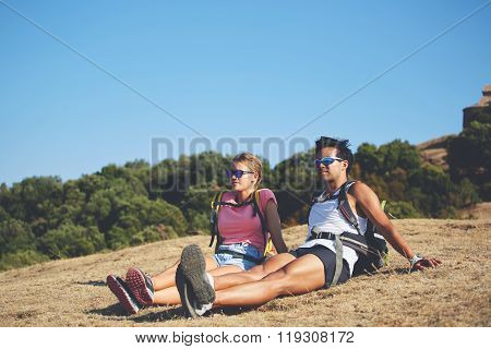 Young man and woman enjoying amazing landscape while sitting on a high mountain in sunny day