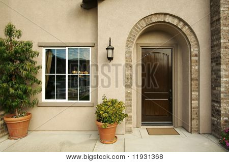 A newly constructed, modern american home doorway and patio.