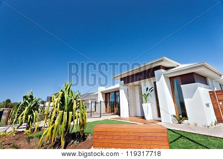 Residential Area With Luxurious Houses And Gardens In The Clear Blue Sky Background