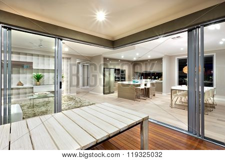 Inside View Of A Modern House Lights Turned On With Wooden Table Surrounded By Glass Doors.