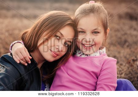lifestyle capture of happy mother and preteen daughter having fun outdoor. Loving family spending ti