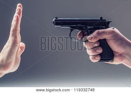 Weapon gun. Men's hand holding a gun. The second hand is defending