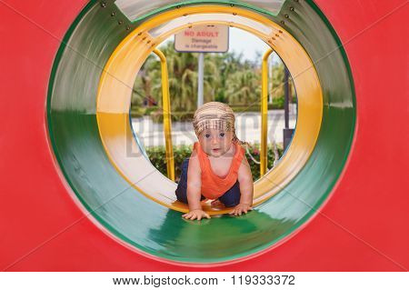 Baby Boy Crawling With Fun Through Colorful Playground Tube
