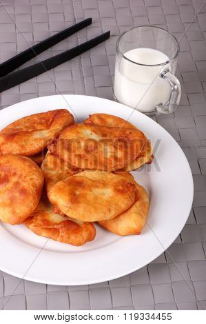 Fried Cakes On White Plate, Kitchen Tongs And Cup Of Milk On Gray Wicker Background