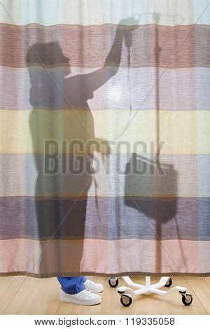 Nurse behind curtain preparing drip