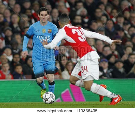 LONDON, ENGLAND - FEBRUARY 23: Lionel Messi of Barcelona runs at Francis Coquelin of Arsenal during the Champions League match between Arsenal and Barcelona at The Emirates Stadium