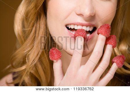 Woman eating raspberries poster