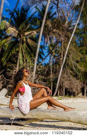 Beautiful Teenage Black Girl Sit On Palm Tree At The Beach.