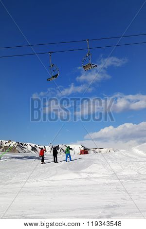 Three Skiers On Slope At Sun Day