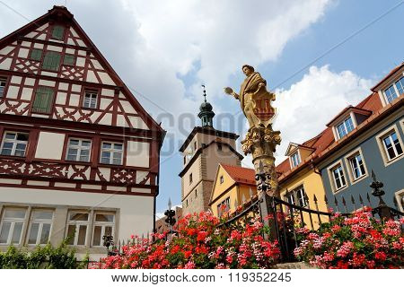 Rothenburg ob der Tauber in Germany. Seelbrunnen fountain on Chapel square. It embodies the Greek goddess Minerva the virgin goddess of wisdom and patroness of the city. poster