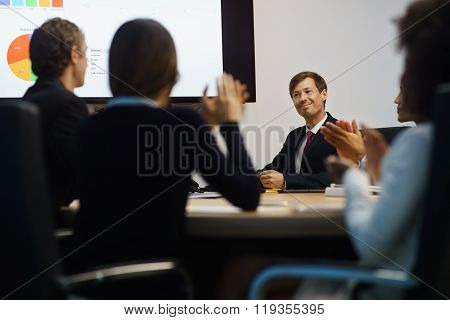 Business People Applauding Manager Doing Presentation In Meeting Room