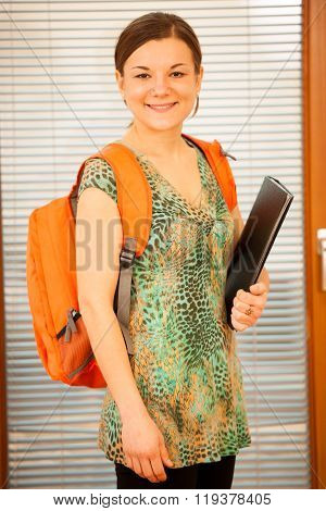 Adult woman representing lifelong learning. Woman with school bag smiling as a gesture of happiness and joy to study.