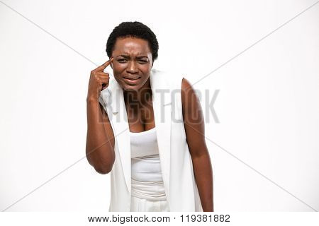 Irritated annoyed african american young woman with finger on temple over white background