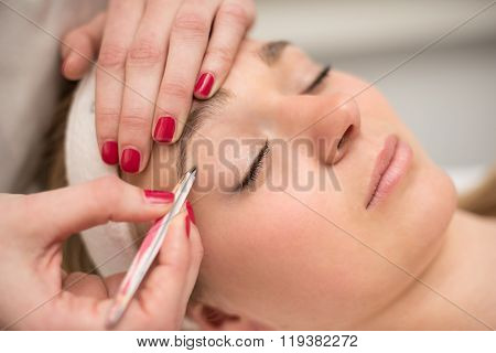 Plucking Eyebrows With Tweezer By Beautician In Beauty Salon.