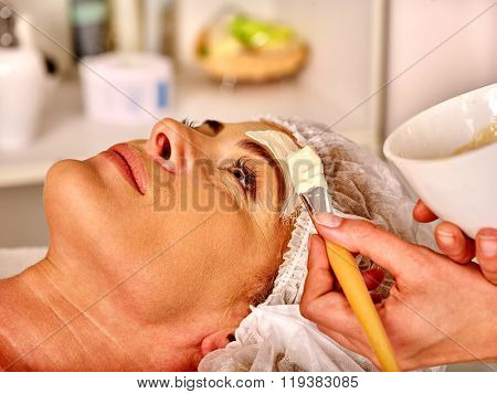 Lying woman middle-aged gets facial and neck clay mask in spa salon.