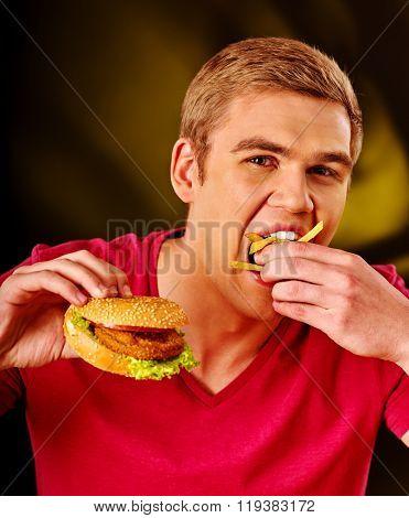 Young man eats greedily big hamburger. Fastfood concept.