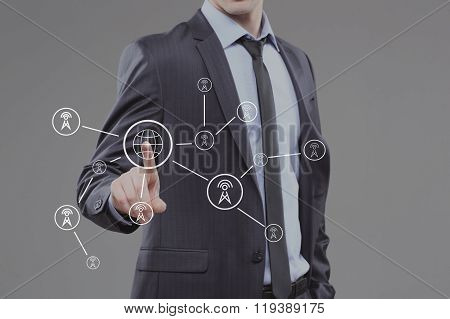 business man pressing a touchscreen button. world map towers