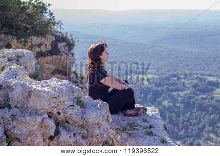 woman in a black tracksuit sitting on the cliff