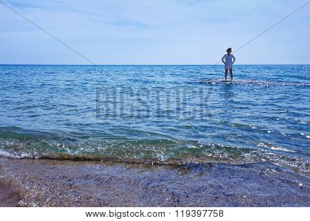 Woman Standing In The Shallow Waters Of The Sea