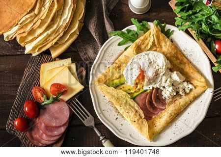 Crepe galette with meat, avocado, soft white cheese and poached egg on white plate. Sliced yellow cheese, pastrami, cherry tomatoes, green salad and stack of crepes on side. Top view
