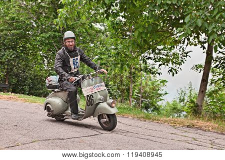 Biker Riding A Vintage Scooter Vespa