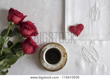 cup of coffee with three red roses and a heart