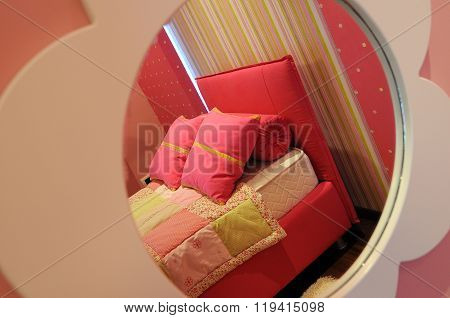 View in mirror of pink bed in bedroom interior