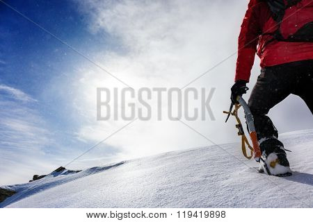 Mountaineer arrive at the top of a snowy peak in winter season. Concepts: determination, courage, effort, self-realization.