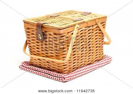 Picknickkorb und gefaltete Decke isoliert auf weißem Hintergrund.