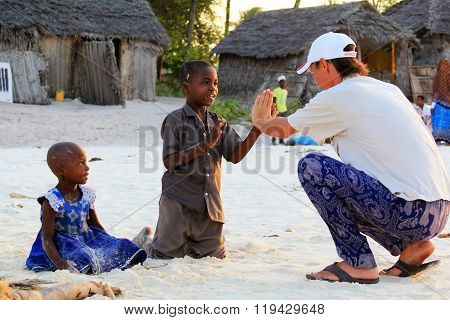 Adult Man Tourist Plays With African Children