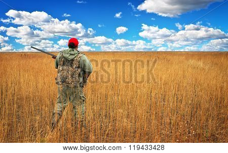 Hunter moving with shotgun looking for prey in the field. Hunter with a gun. Hunting for hare