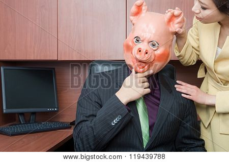 Businessman in pig mask and businesswoman