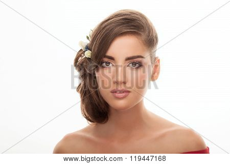 Young adorable brunette lady with cute makeup low bun hairstyle and flower headpiece with bare shou