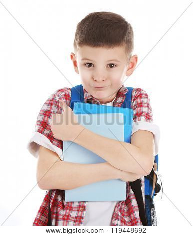 Wary little boy with back pack holding books, isolated on white