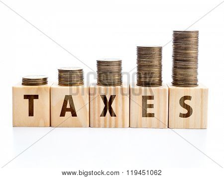 Piles of coins arranged in increased manner placed on wooden block with TAXES word