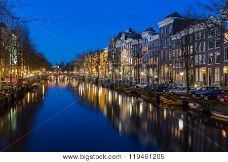 AMSTERDAM NETHERLANDS - 16TH FEBRUARY 2016: A view along the Keizersgracht canal in Amsterdam at night. Reflections buildings and cars can be seen.