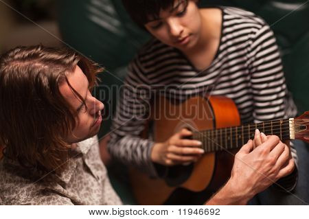 Young Male Musician Teaches Female Student How To Play the Guitar.