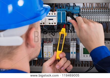 Male Electrician Checking Fusebox