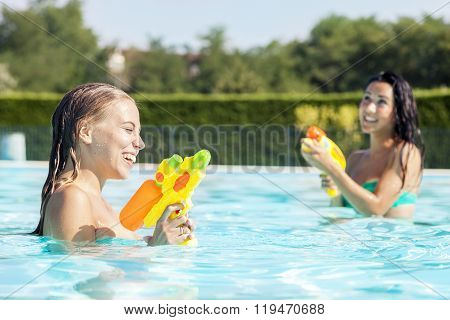 Pretty Girls Playing With Water Guns In Pool