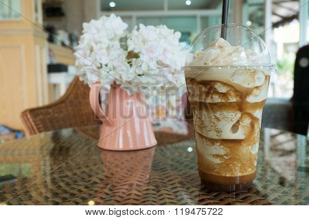 Iced Frappe Coffee In Plastic Mug Put On The Rattan Weave Table In Coffee Shop Cafe