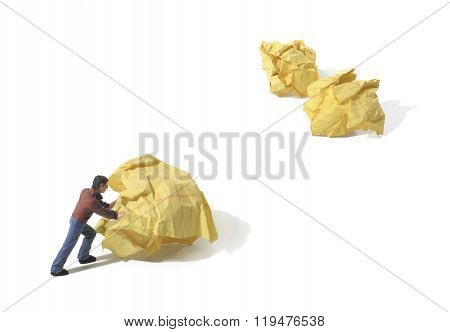 Toy Person Pushing a Wad Of Paper