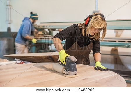 Female carpenter Using Electric Sander