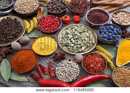 Colorful aromatic Indian spices on a wooden background.