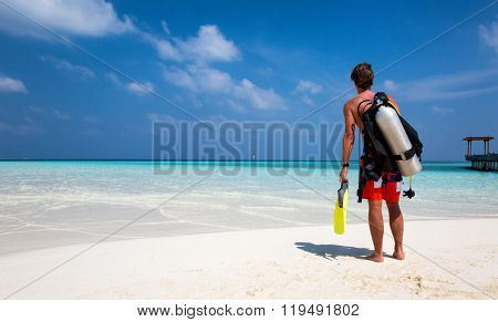 Male scuba diver standing on a beach