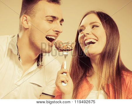 Smiling Woman Feeding Happy Man With Cake.