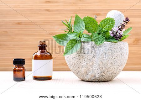 Alternative health care fresh herbs basil ,sage ,rosemary, mint and essential oil with mortar on woo