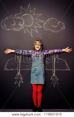 Dream flight. Cheerful girl imagines herself a pilot. Childhood. Fantasy, imagination.