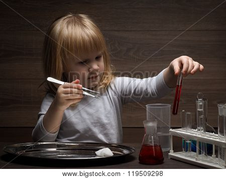 Young child holding forceps and the tube